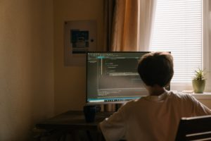 boy in white shirt sitting in front of computer