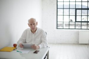 pensive elderly man with tablet working in light workspace